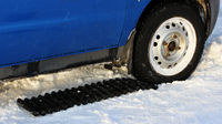 black anti-slip mat of a rectangular shape is placed under the wheel of a low-leveled car after it is stuck in a snowdrift and slips