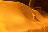 Snowdrift on car after snowfall in night city