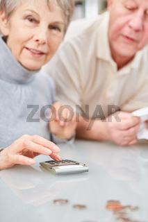 Frau als Rentner mit Taschenrechner