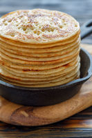 Cast iron pan with stack of fresh pancakes