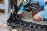 Handwerker lackiert Metall mit einem Flachpinsel schwarz