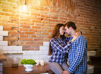 Young couple hugging and kissing at kitchen