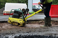 A road construction worker compacts the soil with a compact vibroplate before asphalting a problematic swampy section of the road. Russia, entry in the city of Gatchina