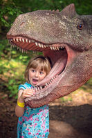 Little girls head in the mouth of a dinosaur
