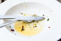 Empty plate with olive oil, herbs and chili leftover