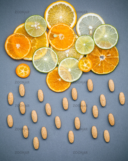 Healthy foods and medicine concept. Pills of vitamin C and various citrus fruits sliced in the shape of cloud and raining. Mixed citrus fruits sliced lime,orange ,kumquat and lemon on gray background.