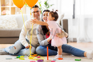 baby girl reaching to balloons at birthday party