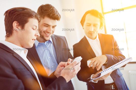 Geschäftsleute bei Termin Planung mit Smartphone