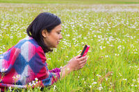 Lying woman phones in blooming pasture