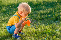 One year old baby boy blowing soap bubbles