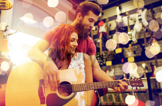 couple of musicians with guitar at music store
