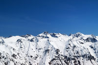 Snow covered mountains and blue sky at sun cold day