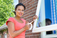 Woman sticking adhesive tape on glass of window