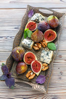 Blue cheese and ripe figs on a bronze tray.