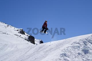Snowboarder jumping in terrain park at ski resort on sun winter day