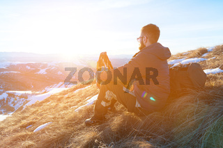 Hipster traveler with a beard and sunglasses sits on a yellow grass on a skew in winter against a background of snow-capped dales