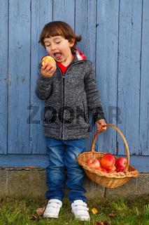 Kind Apfel Obst Früchte essen Ganzkörper draußen Herbst gesunde Ernährung