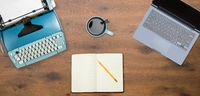 Electric typewriter and laptop on wood background