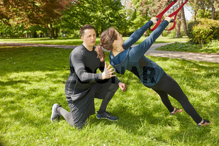 Frau macht Schlingentraining mit Fitnesstrainer