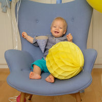 One year old baby boy first birthday. Toddler child sitting in chair.