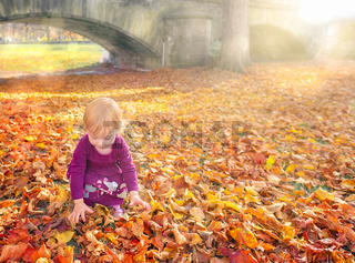 Child playing with hands through fallen leaves