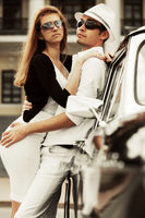 Happy young fashion couple in love by retro car