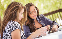 Expressive Young Adult Girlfriends Using Their Computer Electronics Outdoors