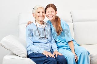 Lächelnde Pflegehilfe und glückliche Seniorin