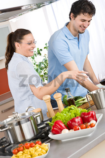 Smiling couple cooking in modern kitchen