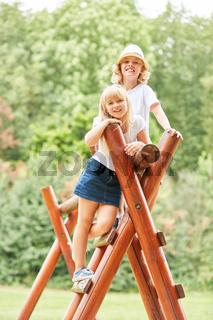 Kinder lächeln stolz auf dem Klettergerüst