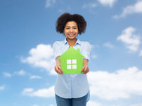 happy african american woman with green house icon