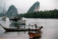 Boote am Krabi-Fluß mit Bergen im Hintergrund