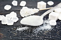 Sugar white in spoon on board