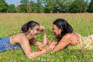 Two friends lying together in green meadow