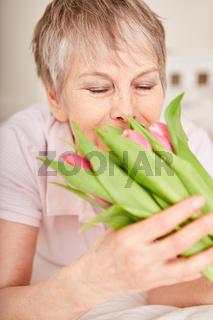 Seniorin freut sich über Blumenstrauß
