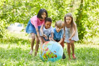 Multikulturelle Gruppe Kinder rollt Weltkugel