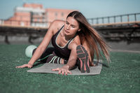 Fitness on the roof, sporty woman stretching.