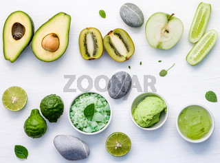 Homemade skincare and body scrubs with green natural ingredients aloe vera ,lime,cucumber ,aromatic salt ,green apple,mint ,kiwi and sage set up on white wooden background with flat lay.