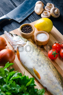 Uncooked fish on cutting board in meal preparation concept