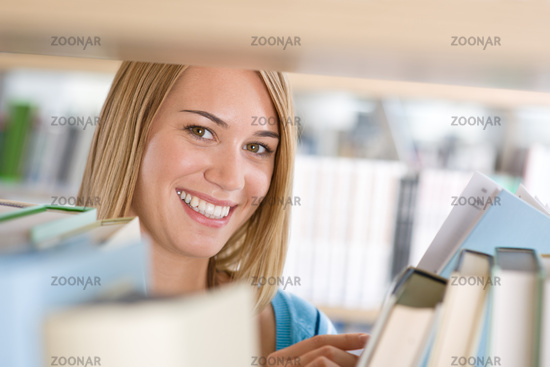 Student in library - cheerful woman look through bookshelf