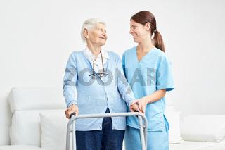 Alte Frau lernt gehen mit Gehgestell in der Reha