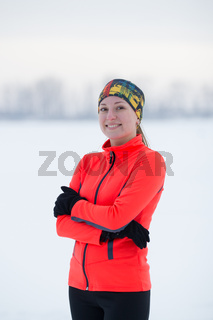 Portrait of a blonde smiling young female sportswoman in winter ice field