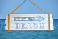 Way to beach sign over blue sky and sea