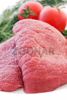 Raw beef fillet with vegetable as closeup on white plate
