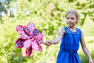 Ein Mädchen spielt mit einem Windrad