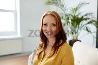 portrait of smiling redhead woman at office