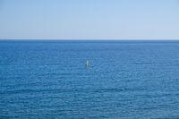 windsurfer far away on ocean horizon