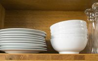 white dishes and glasses in a kitchen shelf