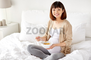 happy pregnant woman eating cereal flakes at home