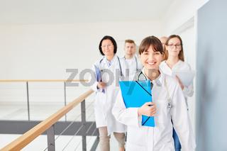 Junge erfolgreiche Ärztin vor ihrem Ärzteteam